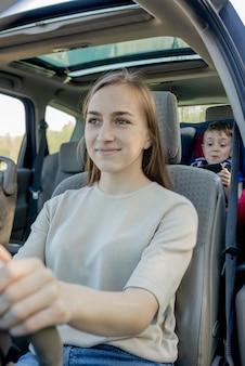 Mère donne le téléphone petit garçon assis dans un siège d'auto. sécurité du transport des enfants.
