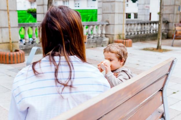 Mère sur le dos avec son fils de trois ans en train de manger des glaces l'après-midi après l'école