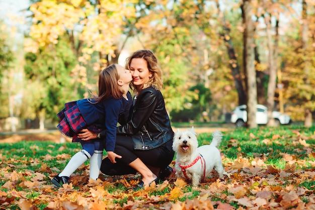 Mère et écolière à la mode marchant avec leur chien dans le parc
