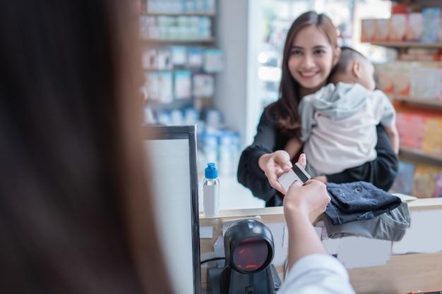 Mère effectuant un paiement au magasin pour bébés à l'aide d'une carte de crédit