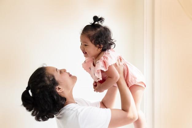Mère élevant sa fille dans les airs