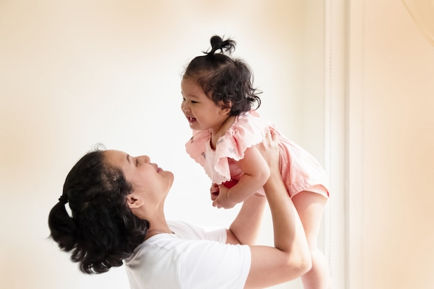 Mère élever sa fille dans les airs, avec sourire et visage heureux