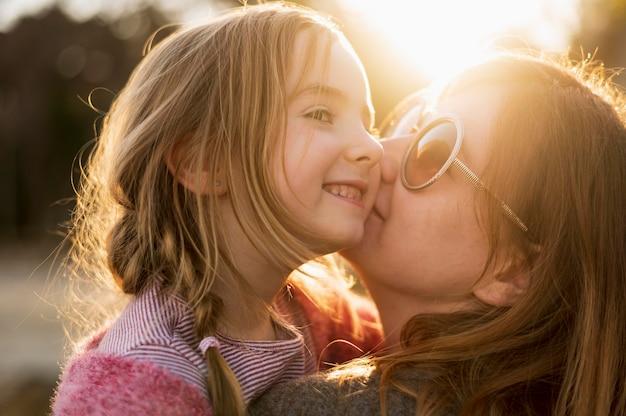Mère embrassant une adorable jeune fille