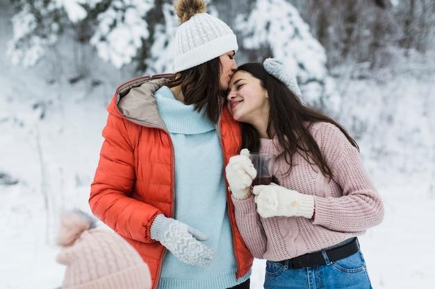 Mère embrassant une fille adolescente
