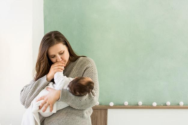 Mère embrassant la main de bébé dans les bras