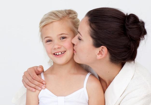 Mère embrassant sa fille dans la salle de bain