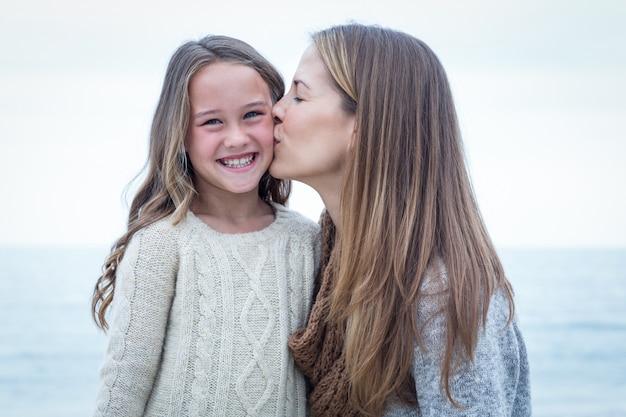 Mère embrassant sa fille à la plage