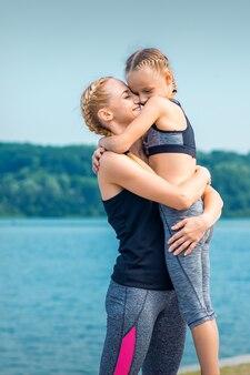 Mère embrassant sa fille près de l'étang portant des vêtements de sport à l'extérieur
