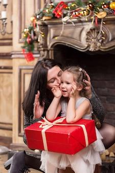 Mère embrassant sa petite fille mignonne avec un cadeau de noël près d'une cheminée avec des décorations
