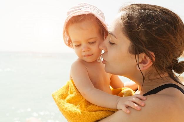 Mère embrassant avec sa petite fille en plein air dans la nature par une journée ensoleillée