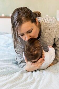 Mère embrasse bébé dans bras