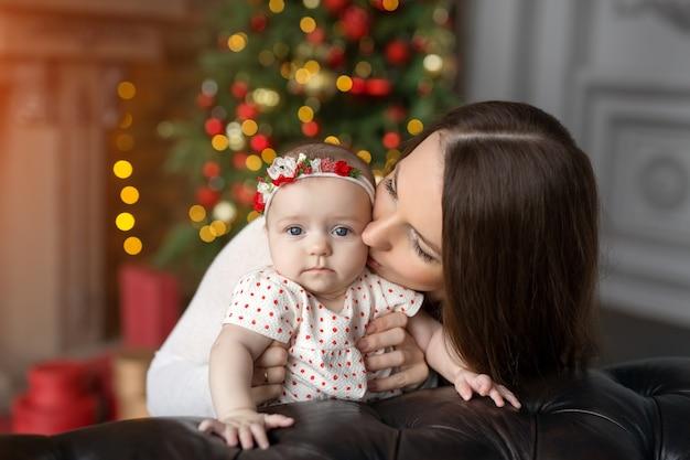 Une mère embrasse un enfant à noël dans une pièce avec des décorations, un sapin de noël et des lumières