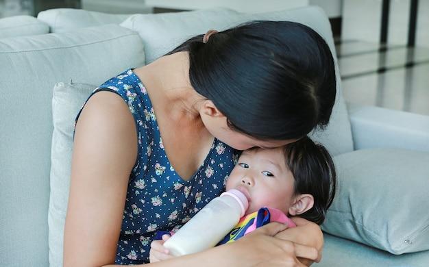 Mère embrasse sa fille enfant buvant à une bouteille sur le canapé