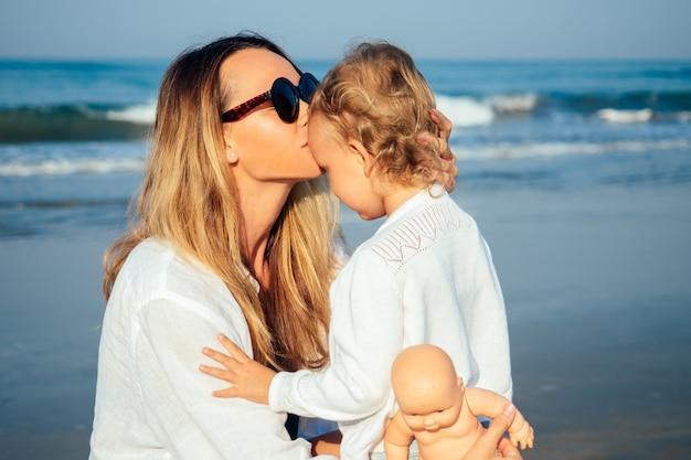 Mère embrasse sa fille le matin sur la plage