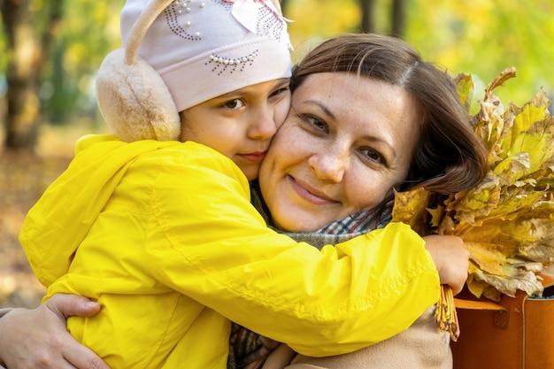 La mère embrasse sa fille, petite fille, avec un sourire en parc d'automne avec des feuilles tombées