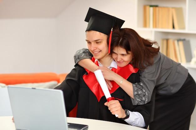 Une mère embrasse son fils étudiant en robe de graduation et une casquette de diplômé tient un parchemin à la main et regarde la diffusion de la cérémonie de remise des diplômes à la maison