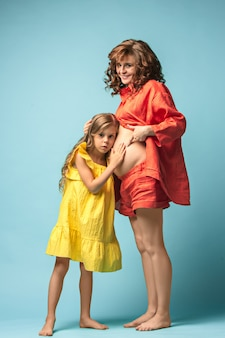 Mère enceinte avec une fille adolescente. portrait de famille en studio