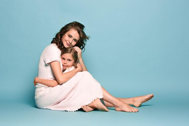 Mère enceinte avec une fille adolescente. portrait de studio de famille sur mur bleu