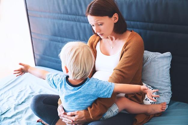 Mère enceinte et fils à la maison enceinte pour la deuxième fois avec premier enfant