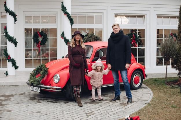 Mère enceinte à la mode, père et fille debout ensemble devant une voiture rétro contre une maison décorée de blanc à noël sous les chutes de neige.
