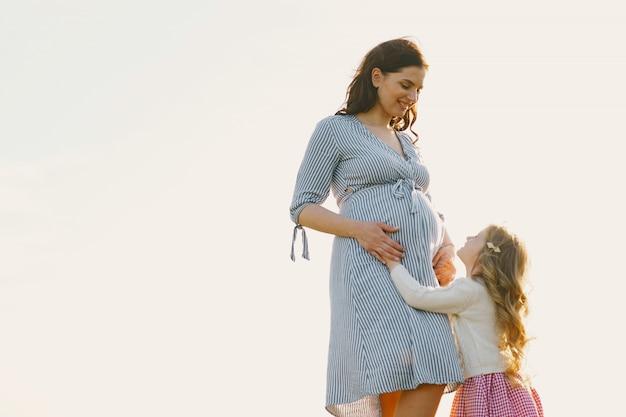 Mère enceinte avec sa fille dans un champ