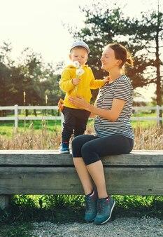 Une mère enceinte et son fils marchent et passent du temps ensemble dans le parc naturel à l'extérieur