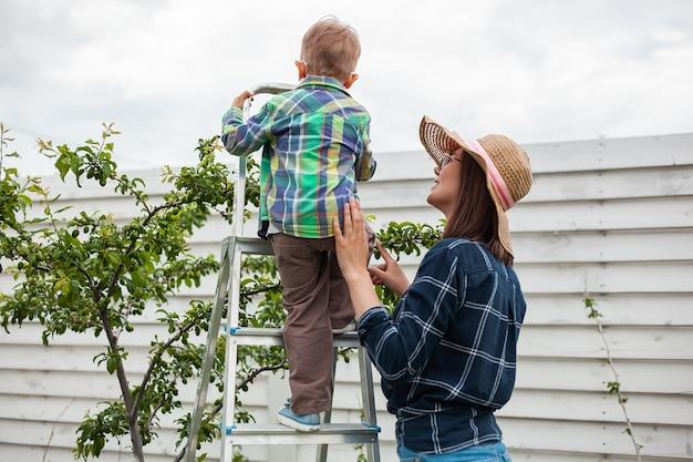 Mère et enfant sur l'arbre de l'échelle, le jardinage dans le jardin d'arrière-cour