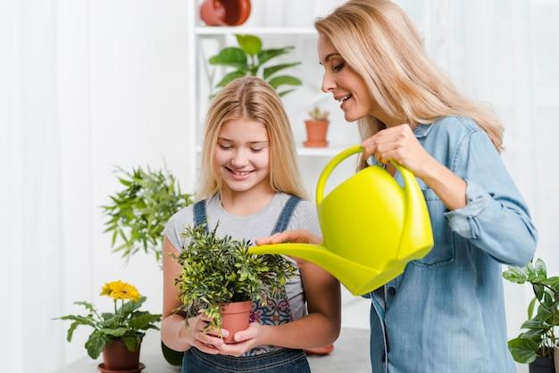 Mère et enfant arrosant des fleurs