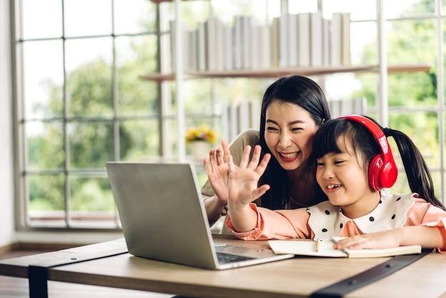 Mère et enfant asiatique petite fille apprenant et regardant un ordinateur portable à faire ses devoirs en étudiant les connaissances avec le système d'apprentissage en ligne de l'éducation en ligne