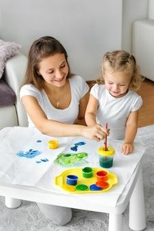Mère et enfant en bas âge peignant à la maison la famille créative