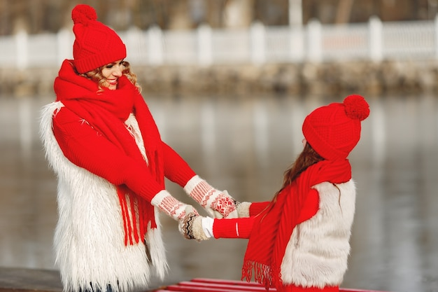 Mère et enfant en chapeaux d'hiver tricotés en vacances de noël en famille. bonnet et écharpe en laine faits à la main pour maman et enfant. tricoter pour les enfants. vêtements d'extérieur en tricot. femme et petite fille dans un parc.