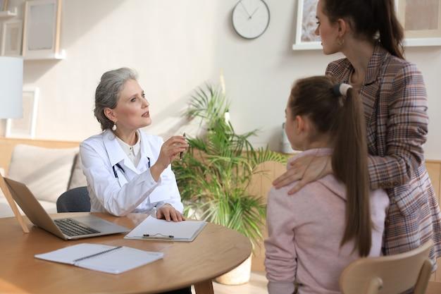 Mère et enfant dans le bureau du médecin rencontrant le pédiatre, ils sont assis au bureau à l'hôpital.