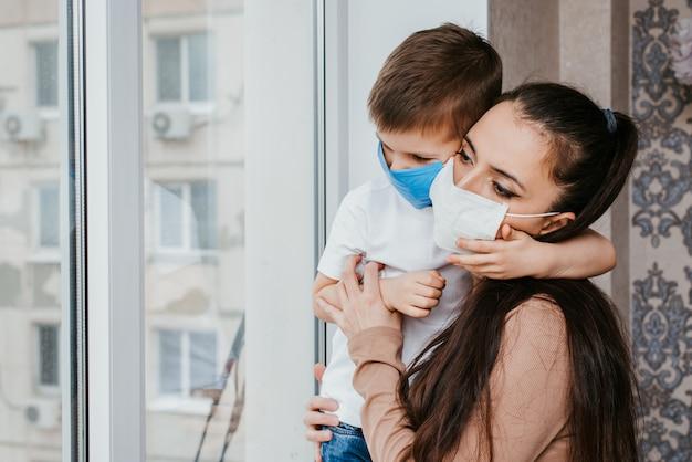 Mère avec un enfant dans des masques médicaux est assise à la maison en quarantaine et regarde par la fenêtre. prévention des coronovirus et covid -19