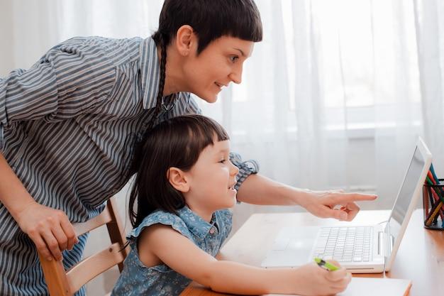 Mère et enfant élève à la maison sur un ordinateur portable apprenant les devoirs à domicile pendant la période de la pandémie et du coronavirus