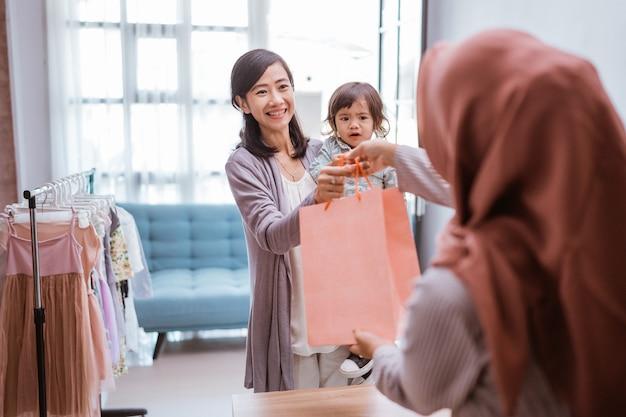 Mère et enfant faisant du shopping dans le centre commercial en achetant des vêtements