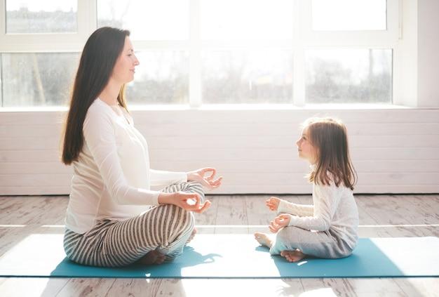Mère et enfant faisant du yoga à la maison