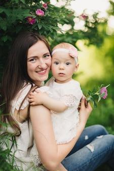 Mère et enfant fille dans le jardin de printemps. jeune femme et petite fille ensemble