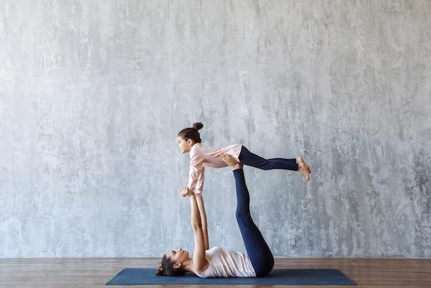 Mère et enfant fille faisant ensemble des exercices de yoga sur le tapis à l'intérieur. sports en famille
