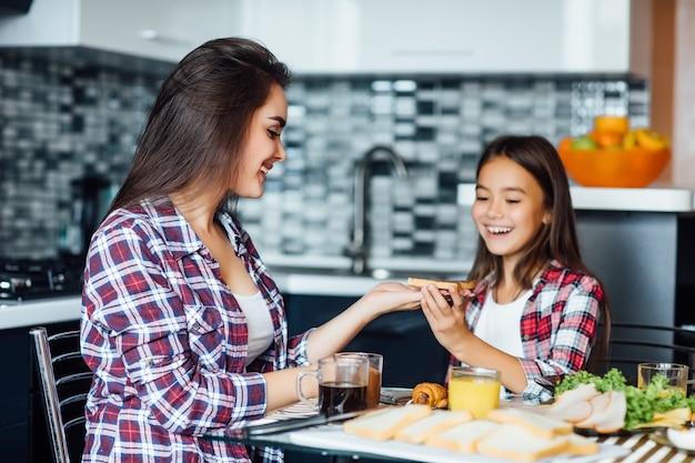 Mère et enfant fille prennent le petit déjeuner avec sandwich