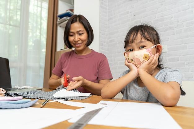 La mère et l'enfant font un masque à la maison