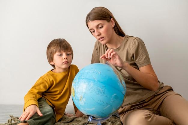 Mère et enfant avec globe à la maison