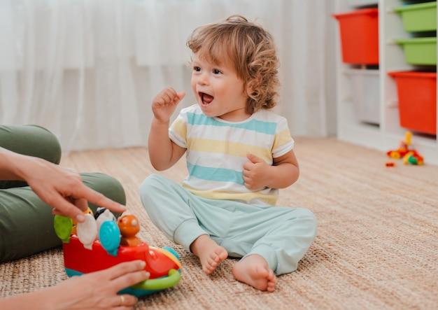 La mère et l'enfant jouent dans la pépinière