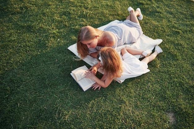 Mère avec un enfant lit un livre sur l'herbe