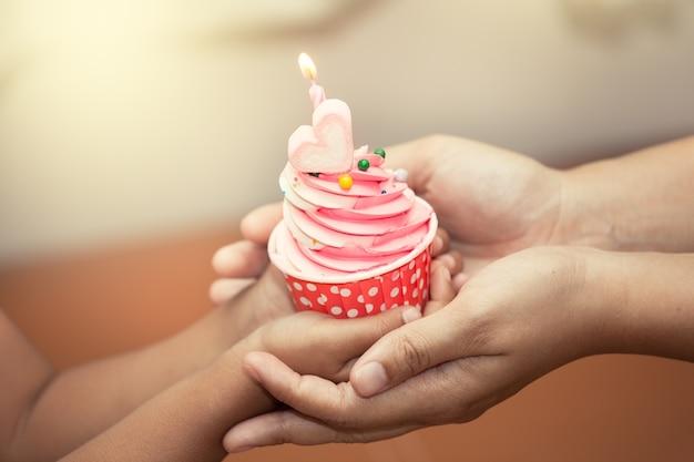 Mère et enfant main tenant le gâteau d'anniversaire dans le ton de couleur vintage