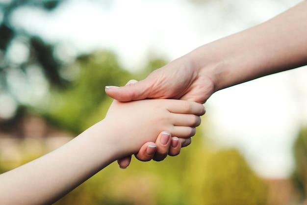 Mère et enfant mains sur fond nature aide et confiance en soutien familial