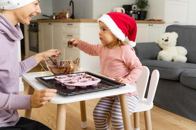 Mère avec enfant prépare des biscuits de vacances à la maison. heureux temps en famille