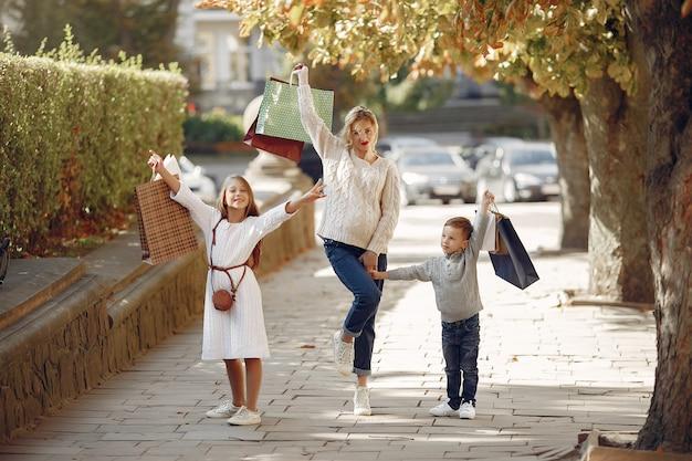 Mère avec enfant avec sac à provisions dans une ville