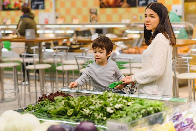 Mère et enfant shopping au marché fermier pour les fruits et légumes