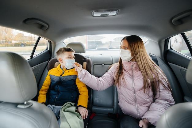 Une mère avec un enfant sur le siège arrière d'une voiture masquée se rendant à l'hôpital.