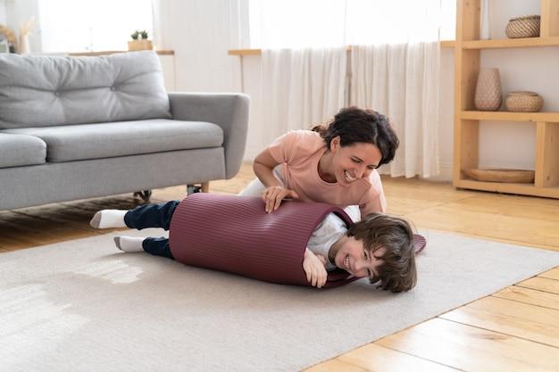 Mère enfant souriant enveloppé dans un tapis de yoga jouant avec son fils